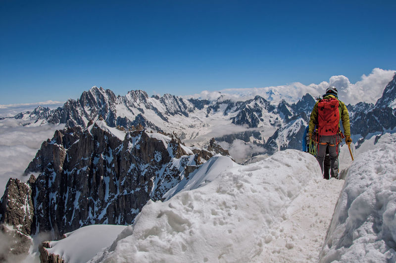 Climbers walking on snowy path in a sunny day at the aiguille du midi, near chamonix, france.