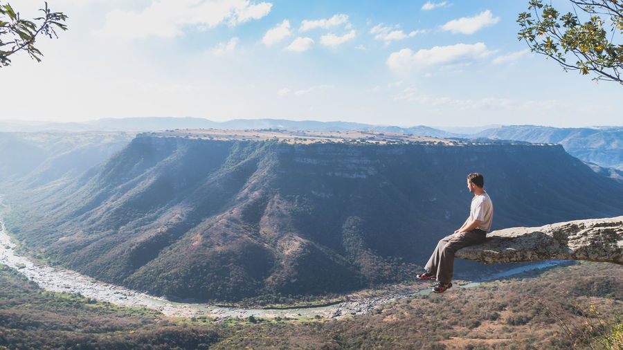 Man sitting on cliff while looking at mountains against sky