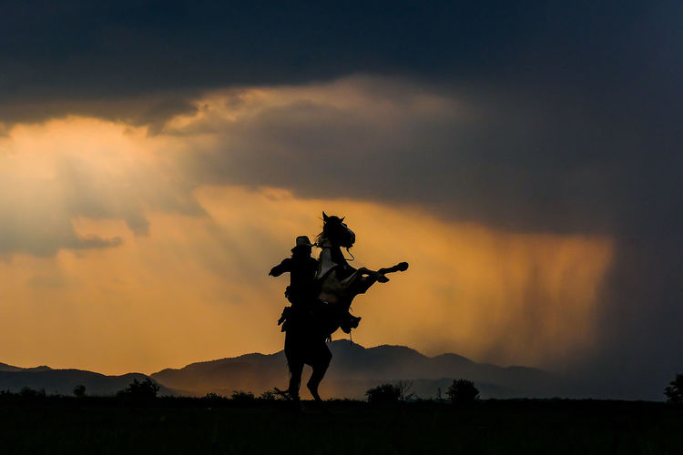 A man in a cowboy outfit with his horse Sky Sunset Cloud - Sky Silhouette Orange Color Nature Mountain Scenics - Nature Beauty In Nature Statue Sculpture Representation Art And Craft Real People Outdoors Land Human Representation Human Arm Men Non-urban Scene Arms Raised