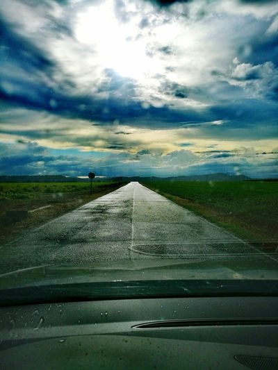 Road against sky seen through car windshield