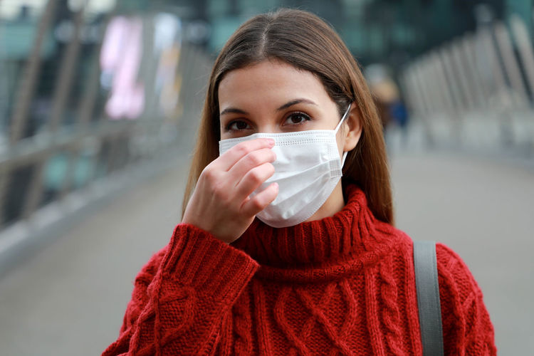 Portrait of young woman in mask standing outdoors
