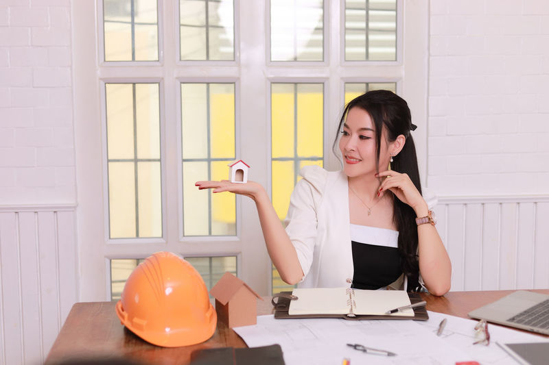 Woman looking at camera while sitting on table