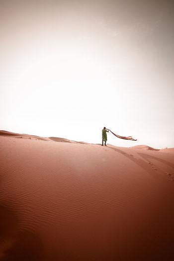 Man on sand dune against clear sky