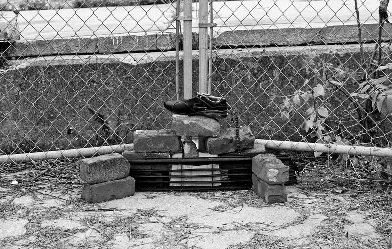 Somebody took the time to put some random things found on the street into an interesting arrangement. Black & White Random Arrangement Arrangement As Found Chainlink Fence Fence No People Outdoors Street Art Unknown Artist