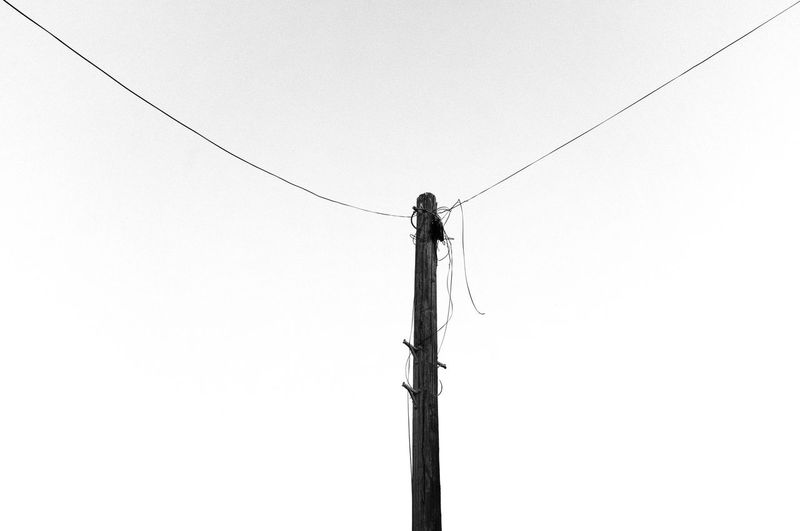 Low angle view of telephone pole against clear sky