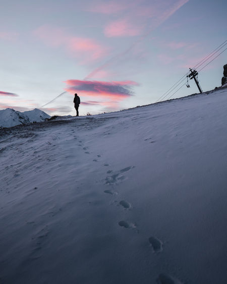 Person on snow covered land against sky during sunset