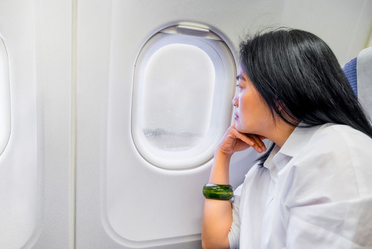 Asian wowan rest hand on chin in airplane cabin near window seat with bad weather raining and feeling worry about dealy flight Alone Asia Woman Bad Weather Delayed Rain Worried Air Vehicle Airplane Commercial Airplane Journey Lifestyles Long Hair One Person Sad Seat Thinkging Transportation Travel Destinations Traveler Window Women