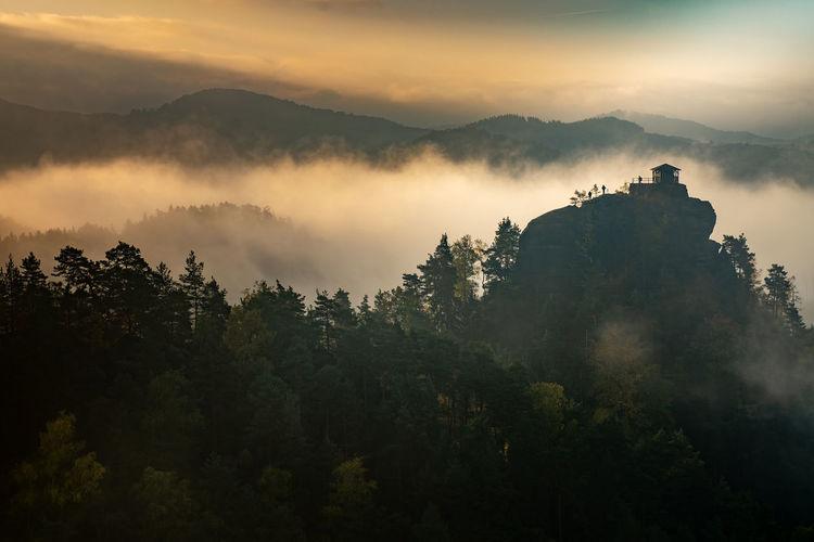 Islands above misty valley, mountain peak with cabin at sunrise. autumn weather with orange mist