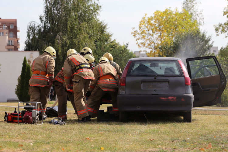 Fire fighters working while standing by car