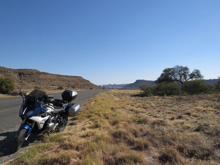 Motorcycle on road amidst field against clear blue sky