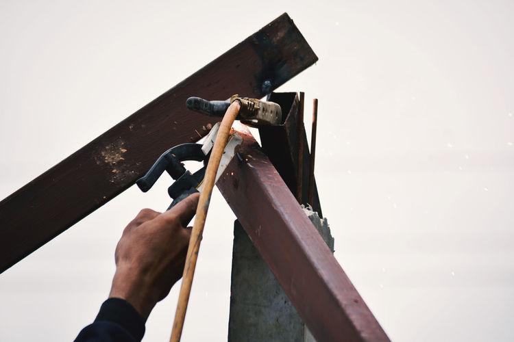 Cropped Hand Of Male Welder Welding Metal Poles Against Clear Sky