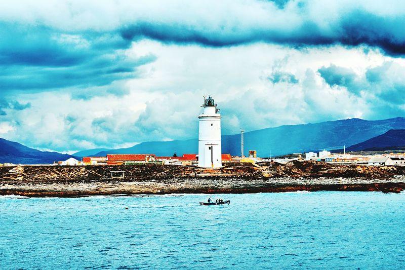 Lighthouse amidst buildings by sea against sky
