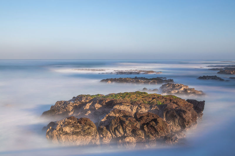 High Angle View Of Rocks At Coastline Surrounded By Fog