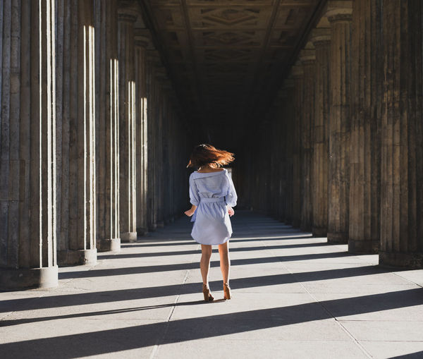 Rear view of woman standing at colonnade