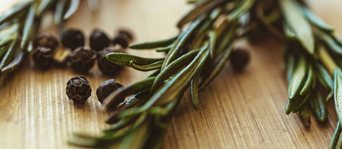 High Angle View Of Black Peppercorns And Rosemary On Table