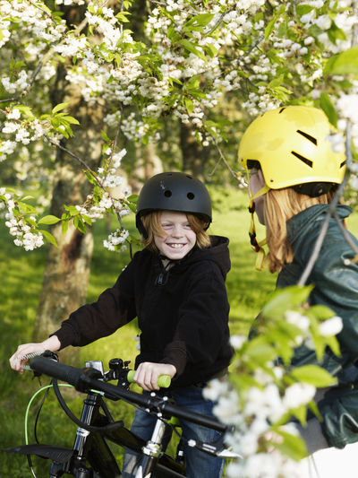 Boy riding bicycle on plants