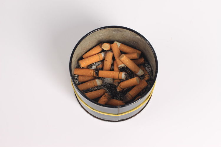 High Angle View Of Cigarettes In Container Over White Background
