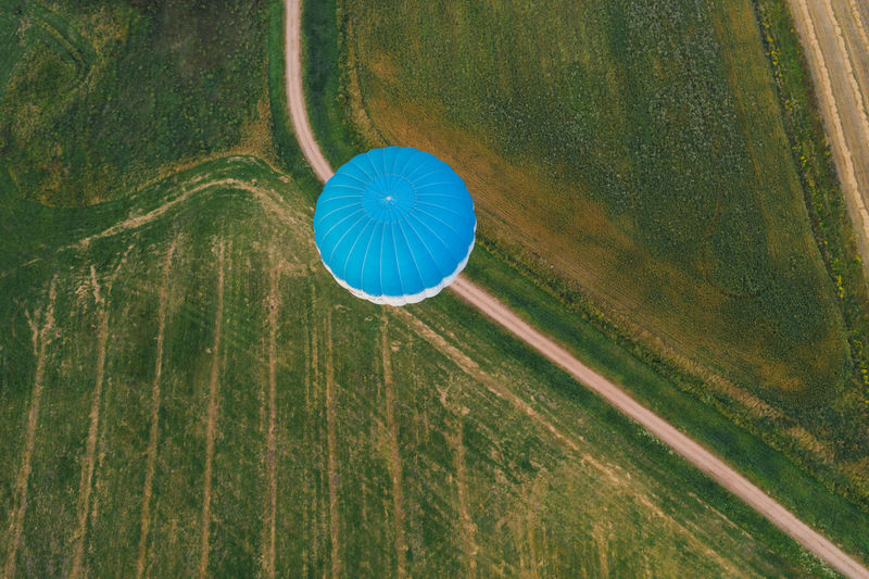 High angle view of plant on field flying in a blue hot air balloon over the fields of belarus