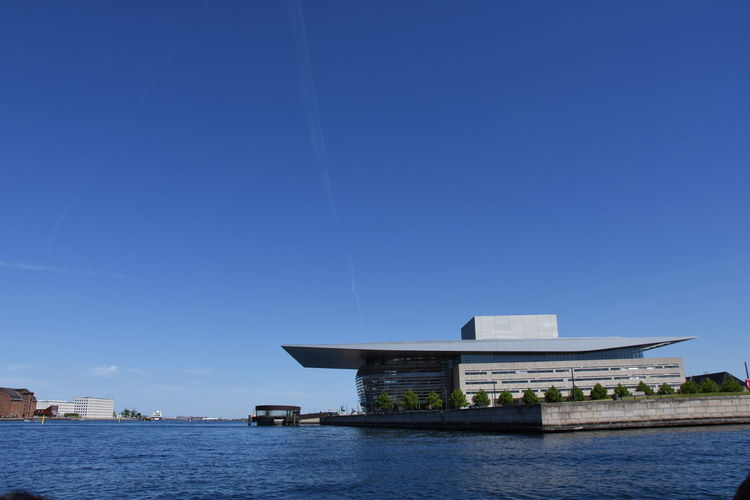 Building by sea against clear blue sky