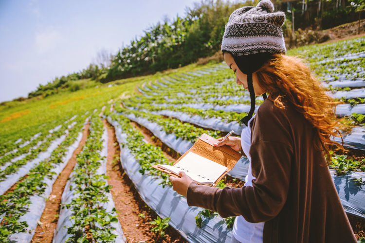 Woman wearing knit hat holding book while standing on field