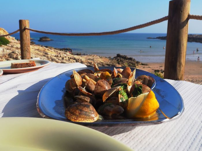 Close-up of breakfast on table by sea against sky