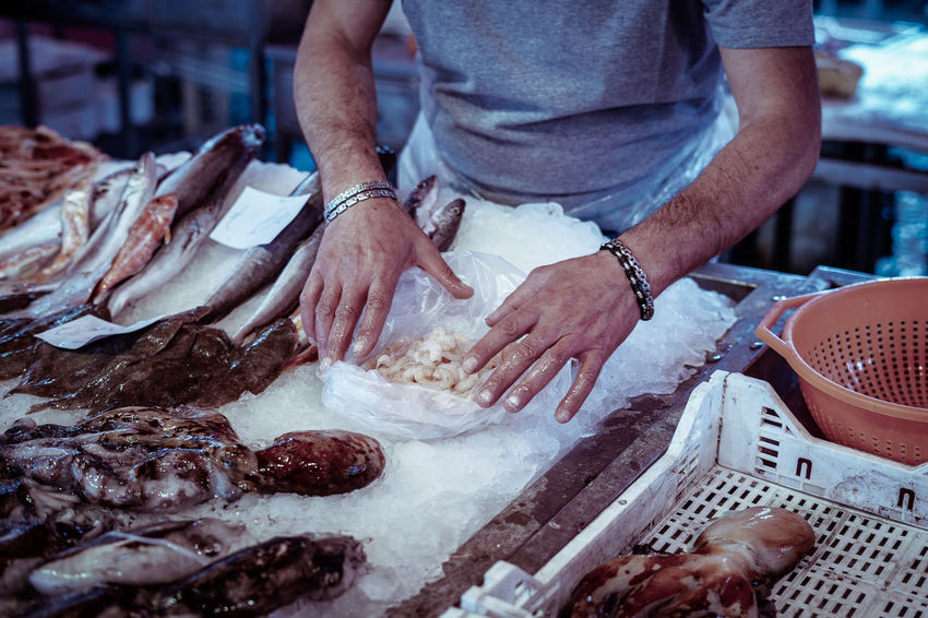 A fishmonger prepares shrimps in a bag for sale Ice Shrimps Cutting Fish Market Fish Monger Food Food And Drink Freshness Hand Human Hand Indoors  Making Market Stall Meat Men Midsection Occupation One Person Preparation  Preparing Food Raw Food Real People Stall Standing Working