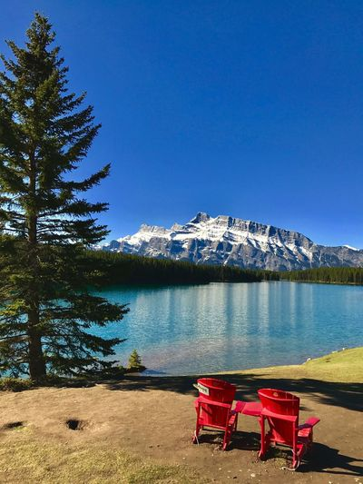 Empty red adirondack chairs at lakeshore against mt rundle during winter