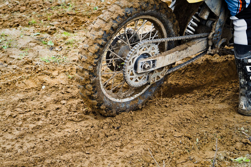 Low section of person riding motorcycle on dirt road