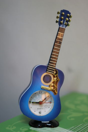 Close-up of toy guitar clock against gray background