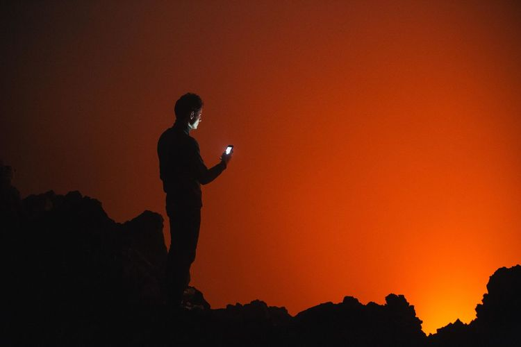 Silhouette man using mobile phone while standing on rocks during sunset