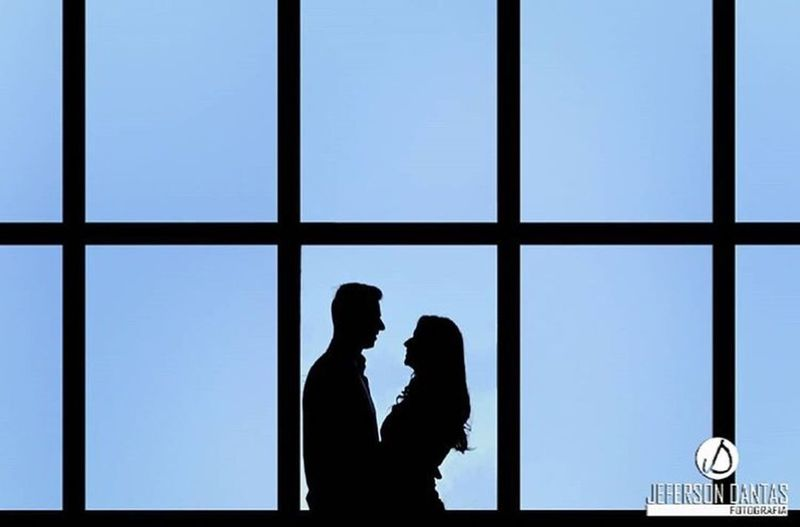 Silhouette couple standing against blue sky seen through window