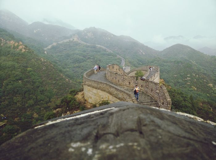 Tourists At Great Wall Of China Against Sky
