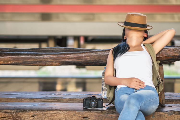 Woman With Hat And Camera Relaxing On Wooden Bench