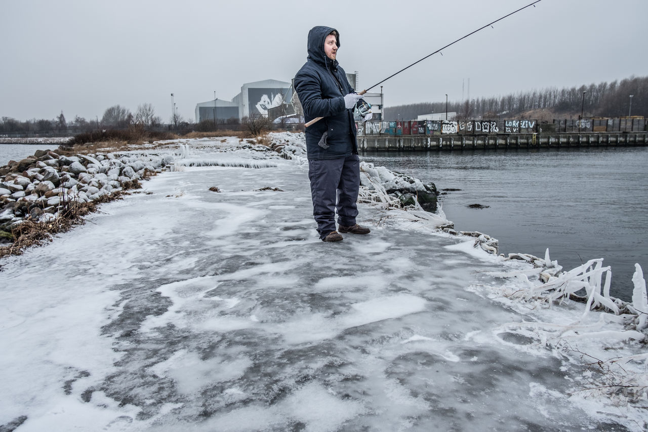 real people, one person, standing, holding, water, casual clothing, full length, lifestyles, outdoors, winter, cold temperature, working, sky, day, nature, occupation, clear sky, warm clothing, young adult