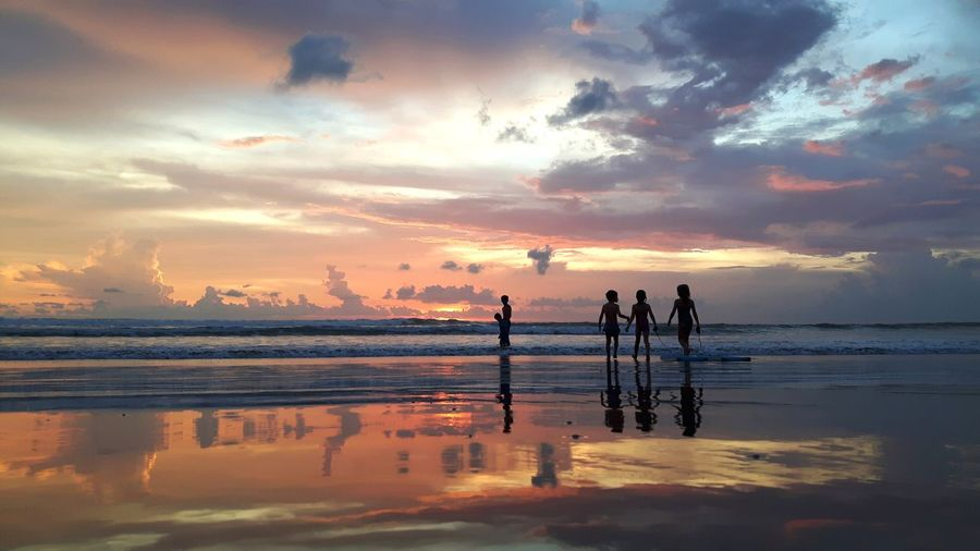 Silhouette Children At Beach Against Cloudy Sky During Sunset