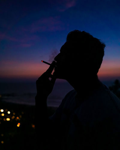 Silhouette man smoking cigarette against sky during a moody sunset.
