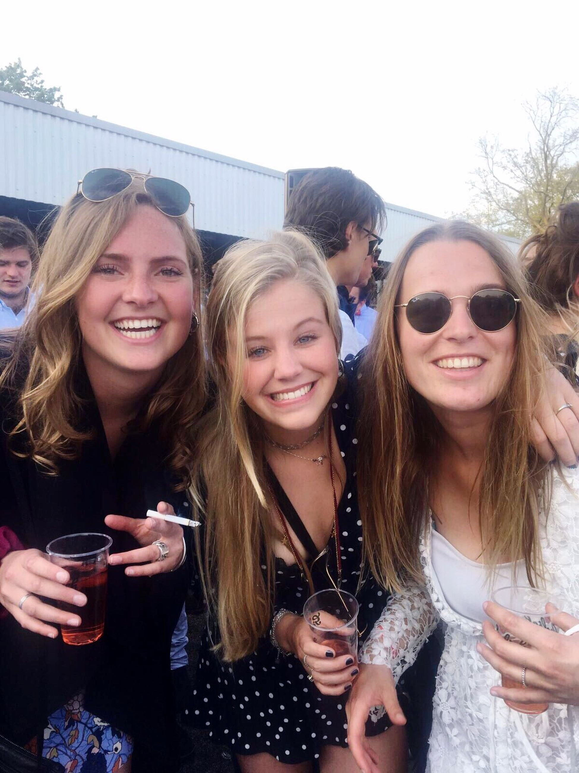 drinking, friendship, smiling, drink, real people, togetherness, food and drink, leisure activity, looking at camera, portrait, holding, alcohol, happiness, day, outdoors, young adult, young women