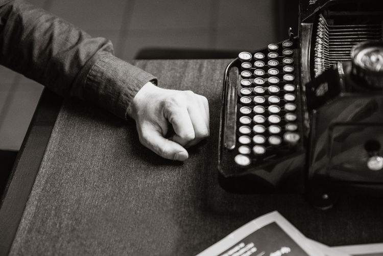 High angle view of male author resting hand at desk by antique typewriter