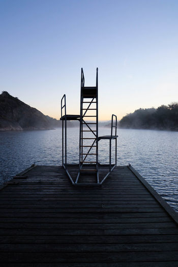 Diving platform on jetty over lake against sky during sunset
