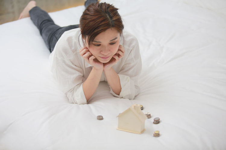 High angle view of looking at model house with coins while lying on bed at home