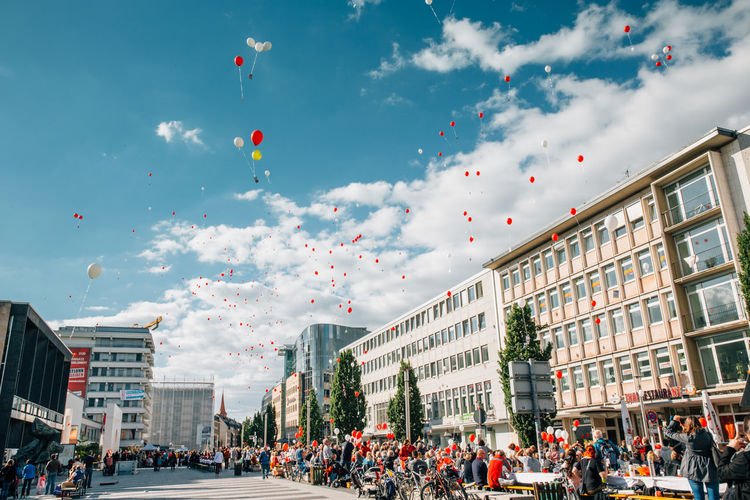 Low Angle View Of Balloons Flying Over Crowd And Street Amidst Buildings On Sunny Day