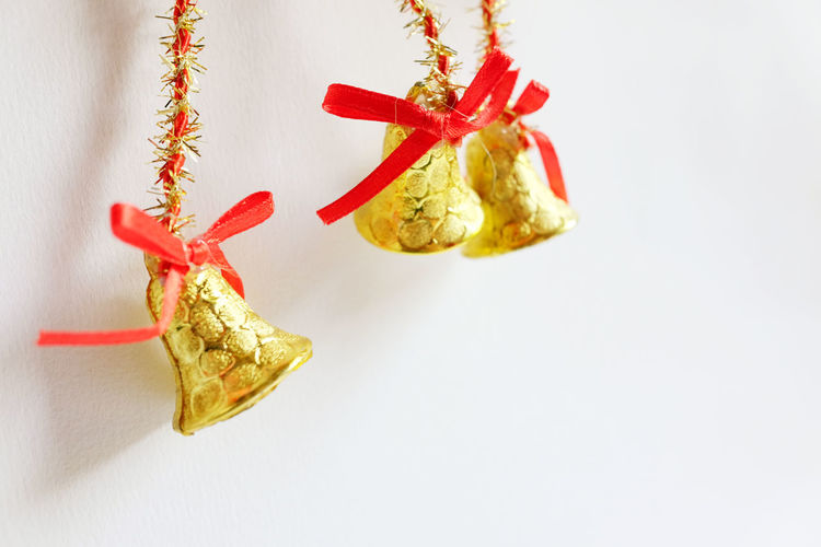 Close-up of christmas bells hanging against white background