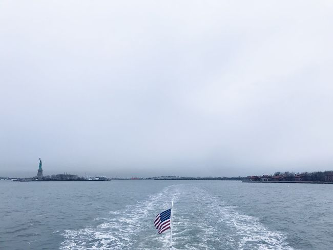 statue of liberty and ellis island Ellis Island  Statue Of Liberty Statue American Flag Water Nautical Vessel Day Nature Outdoors Sky Sea Sailing Beauty In Nature No People