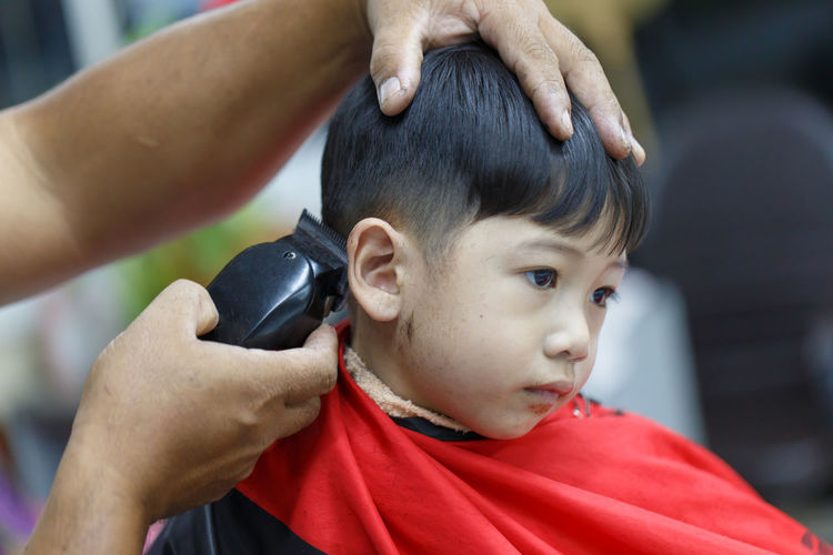 Cropped hand of barber cutting boys hair