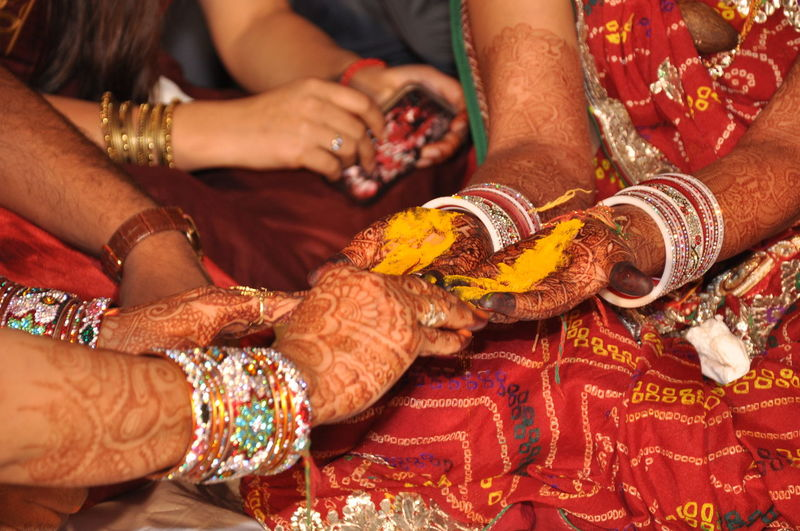 Woman performing rituals on bride during wedding