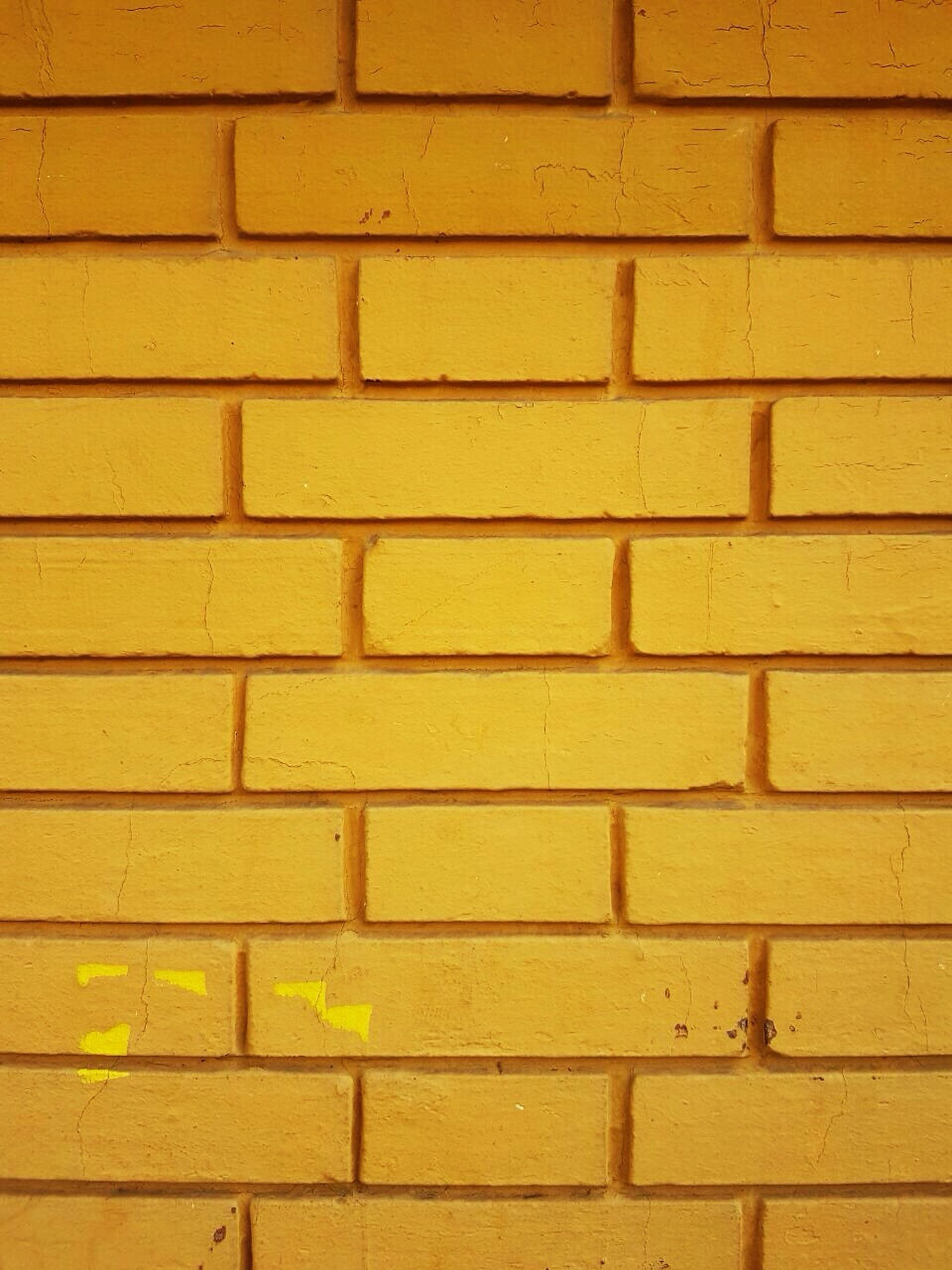full frame, backgrounds, textured, pattern, yellow, built structure, wall - building feature, brick wall, architecture, close-up, no people, wall, building exterior, outdoors, day, repetition, detail, orange color, design, geometric shape