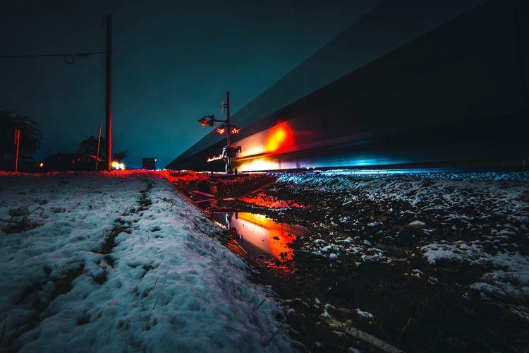 Illuminated road by sea against sky at night