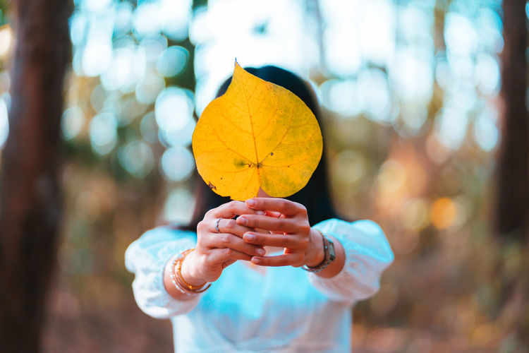 Midsection of woman holding yellow leaf during autumn