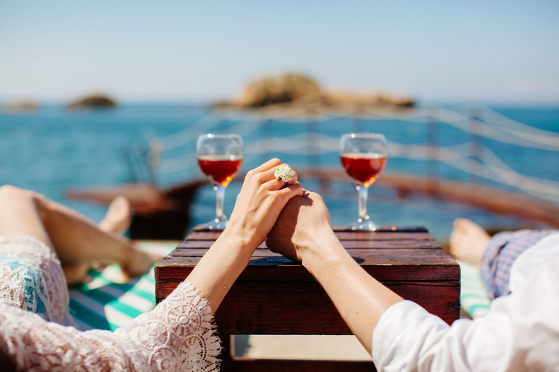 couple drink wine at seaside. Vacations honeymoon Alcohol Beach Close-up Day Drink Food And Drink Holding Human Body Part Human Hand Leisure Activity Lifestyles Low Section Men Outdoors Real People Red Wine Refreshment Sea Togetherness Two People Vacations Water Wine Wineglass Women