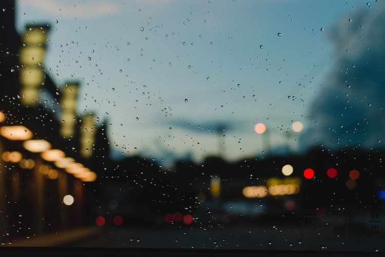 City seen through wet glass window at night